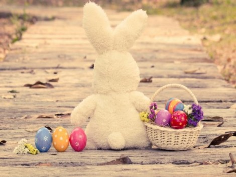 Colorful easter eggs in basket with cute rabbit on wooden pathway in vintage style